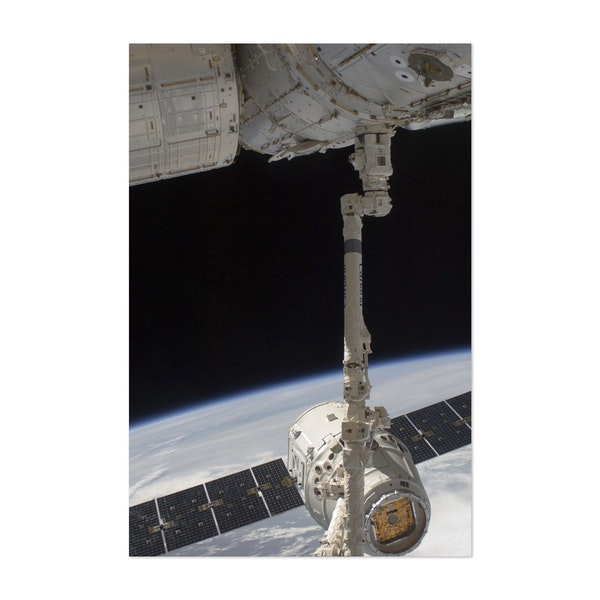 The SpaceX Dragon commercial cargo craft is grappled by the Canadarm2. by Stocktrek Images